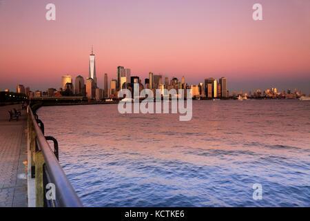 Sonnenuntergang Blick auf Lower Manhattan Finanzviertel mit Hudson River im Vordergrund. New York City, USA - Stockfoto