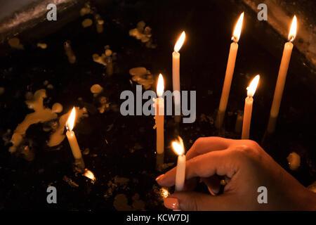 Frau hand Kerze in der Kirche. - Stockfoto