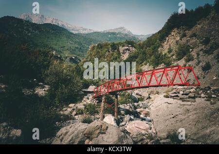 Rote Brücke über den Fluss im Tal thethi thethi, Albanien. - Stockfoto
