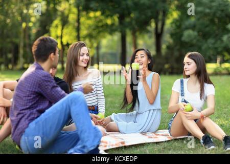 Freunde auf Picknick, junge Mann wirft einen Apfel zu Frau. Studenten Spaß am Mittagessen im sonnigen Park. Menschen - Stockfoto