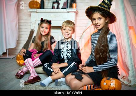 Portrait von drei Kindern tragen Halloween Kostüme posiert auf Kamera sitzen auf dem Boden in eingerichtete Studio - Stockfoto
