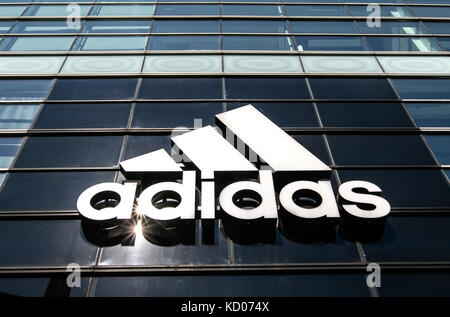 Die Sonne scheint hell auf einem großen Adidas Logo auf der Außenseite ihrer Store auf Houston Street. - Stockfoto