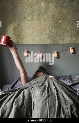 Frau im Bett, versteckt sich unter Abdeckungen, holding Becher in Luft - Stockfoto