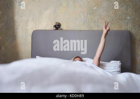 Frau im Bett, versteckt sich unter Abdeckungen, Arm in der Luft, Hand, Frieden Zeichen - Stockfoto