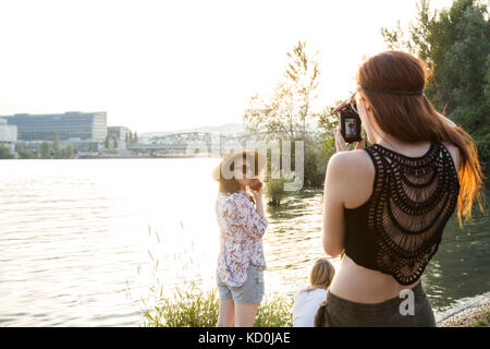 Drei weibliche Freunde im Water's Edge, junge Frau Freunde fotografieren - Stockfoto