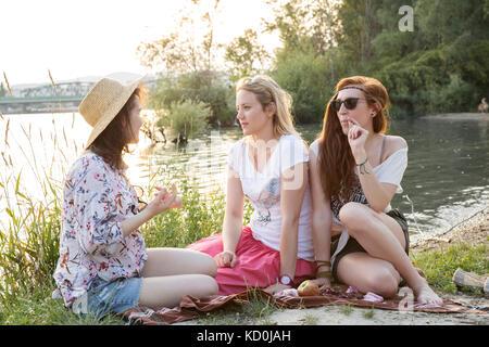 Drei weibliche Freunde Entspannen am See - Stockfoto