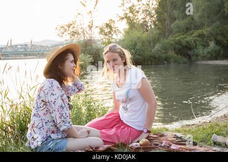 Zwei weibliche Freunde Entspannen am See - Stockfoto