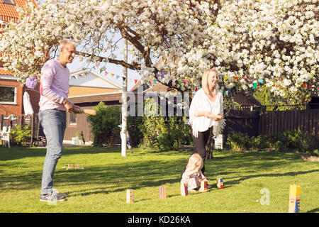 Mädchen (18-23 Monate) Spielen auf Gras und Eltern spielen Kubb - Stockfoto