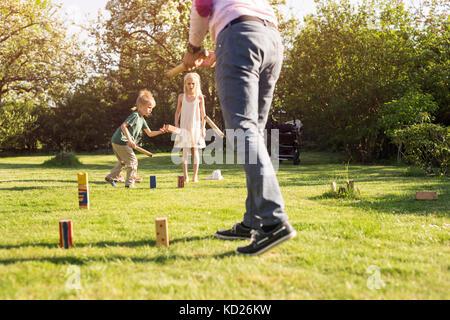 Kinder (4-5, 8-9) Kubb spielen - Stockfoto