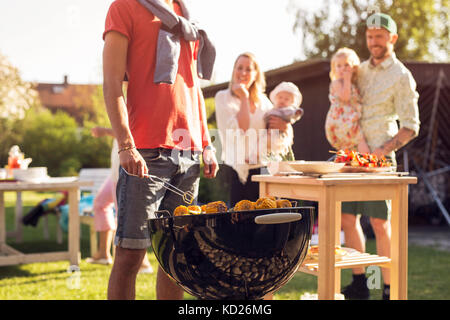 Mann und Frau mit Kindern (2-5 Monate, 18-23 Monate) beobachten junge Mann am Grill - Stockfoto