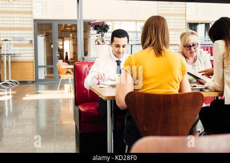Vier Kollegen das Mittagessen in der Cafeteria - Stockfoto