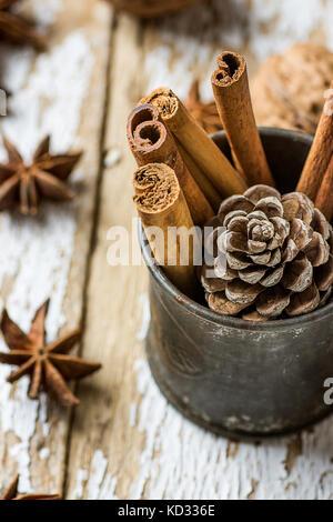 Weihnachten backen Zutaten Cinnamon Sticks verstreut Anis Sterne Walnüsse Kegel in Vintage kanne Kiefer auf Holz - Stockfoto
