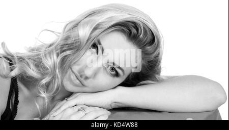 Schwarz-weiß Foto von einer schönen jungen Frau Festlegung auf ihre Hand über Weiß isoliert - Stockfoto