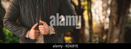 Portrait des jungen Mannes posieren, während gegen den weißen Hintergrund gegen Fußweg ständigen von Bäumen in der - Stockfoto