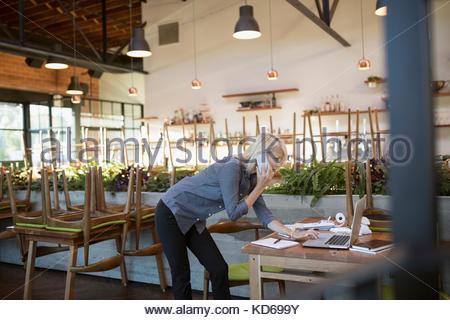 Weibliche cafe Geschäftsinhaber Gespräch am Handy, am Laptop arbeiten - Stockfoto