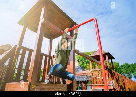 Ein neugieriger Offenes kleines Mädchen klettern auf dem Spielplatz allein bei schönem Wetter - Stockfoto