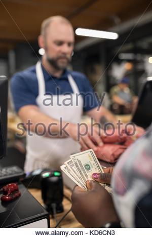 Kunden mit Bargeld bezahlen Metzger in Metzger - Stockfoto