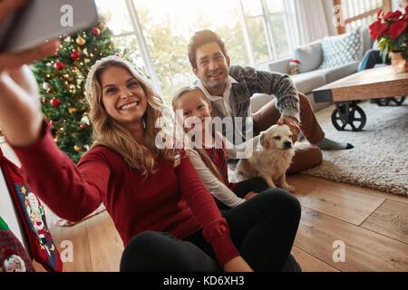 Junge, glückliche Familie von drei ein Foto von sich selbst im Wohnzimmer am Heiligabend. Kaukasische Familie mit - Stockfoto