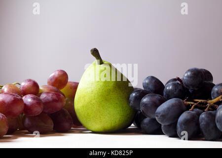 Früchte auf einem hölzernen Hintergrund. Mango, Kiwi, Mandarine, Zitrone, Birne, Traube, Kaki, Apple. - Stockfoto