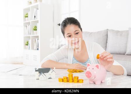Reizende junge Frau im Wohnzimmer zu Hause sitzt und die Goldmünze Geld sparen in rosa Sparschwein für den Kauf - Stockfoto