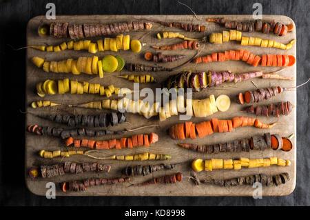 Ein Array von Rainbow Karotten in vielen Formen und Farben, alle fein auf einen verschlissenen Holz Hackklotz gehackt. - Stockfoto