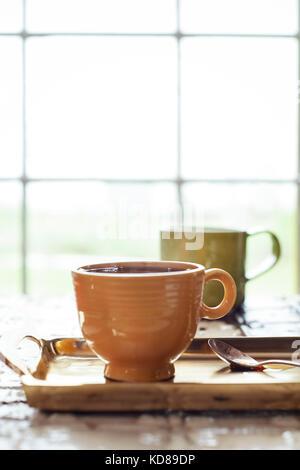 Zwei heiße Tassen Kaffee auf einem goldenen Tablett vor einem Fenster mit warmen Morgen bringen Licht in Gießen. Stockfoto