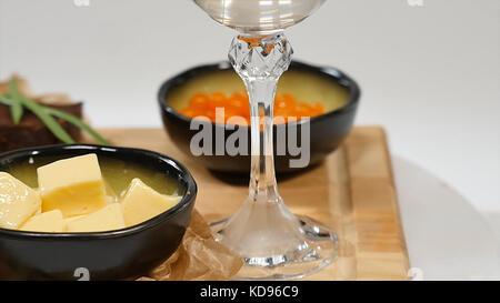 Snacks, Sandwiches mit Butter, roter Kaviar, knusprigem Baguette und Wein auf weißem Hintergrund. roter Kaviar. - Stockfoto