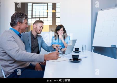 Drei Lächeln Geschäftsleute mit einem Laptop zusammen in einem Büro - Stockfoto