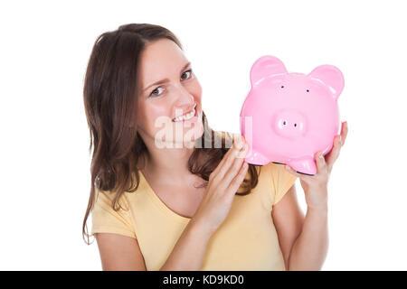 Close-up mit einem lächelnden Frau mit Sparschwein auf weißem Hintergrund - Stockfoto