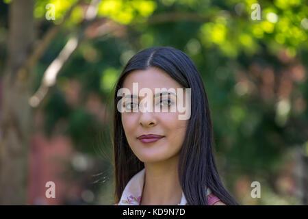 Portrait von schönen Mädchen mit Seidigen dunkles glattes Haar in Park posing - Stockfoto