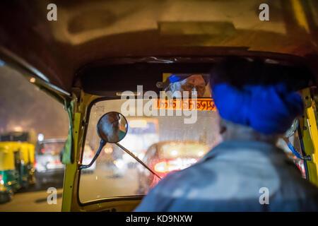 AGRA - Indien am 6. Dezember 2017. Eine Rikscha (auch als Tuc Tuc bekannt) Treiber ist das Fahren in den Straßen von Agra in Indien in der Nacht. Agra ist eine Stadt auf der Ba
