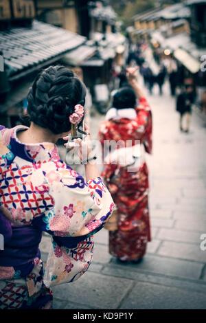 KYOTO, Japan - 10. JANUAR 2016: Japanische Mädchen im traditionellen Kimono sind unter Fotos eine selfie auf dem - Stockfoto