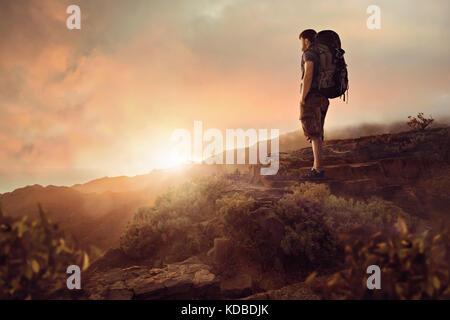 Mann mit einem Rucksack, einer epischen Sonnenuntergang - Stockfoto