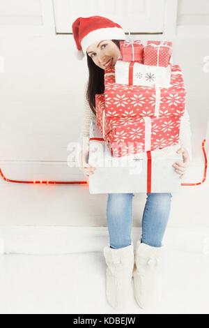 Frau Blick aus einem Haufen von Weihnachten Geschenkboxen - Stockfoto