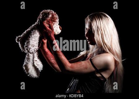 Blutige junge Frau mit einem Teddybär auf schwarzem Hintergrund - Stockfoto