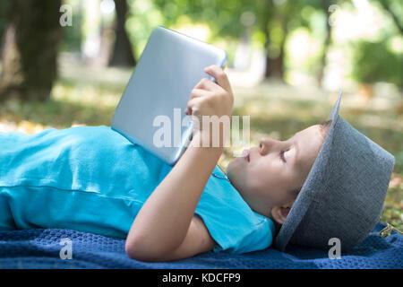Kleinen Niedlichen Jungen im Vorschulalter nutzt ein digitales Tablet beim Liegen auf dem Rasen. Er sieht auf seine - Stockfoto