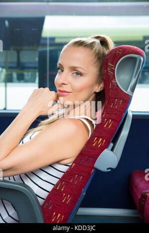 Eine junge Frau sitzt bequem auf dem Bus.