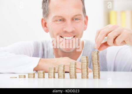 Portrait von Happy reifer Mann zu Hause sitzen stapeln Münzen - Stockfoto