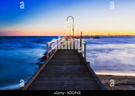 Hellen, warmen über Meer in Port Melbourne Beach Holzsteg mit Blick auf ruhig fliessend Wasser der Port Philip Bay. - Stockfoto