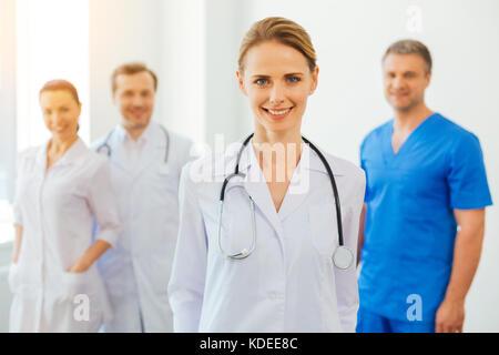 Positiv gesinnten weiblichen Praktizierenden mit Stethoskop posieren für die Kamera - Stockfoto