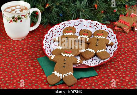 Gingerbread man Cookies in weihnachtlicher Atmosphäre mit einer Tasse heißer Schokolade. - Stockfoto