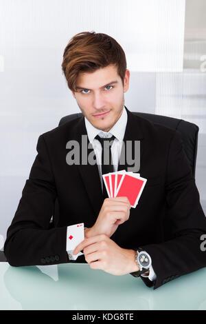 Portrait einer jungen Geschäftsmann mit Spielkarten in der Hülse - Stockfoto