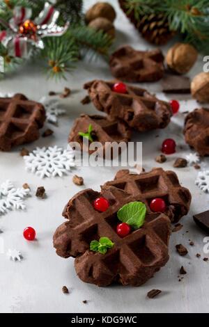 Hausgemachte belgische Schokolade Waffeln mit frischen Beeren und Minze auf grauem Stein oder Schiefer Hintergrund Weihnachten Hintergrund.