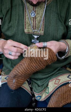 Mittelalterliche person ausbessern Wollsocken zu einem fairen. 7/8 shot zeigen Hände mit wool Socke es ausbessern. - Stockfoto