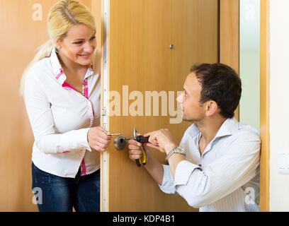 Glückliches junges Paar zur Festsetzung der Tür zu Hause. Konzentrieren Sie sich auf die Mann - Stockfoto