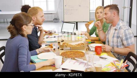 Junge Menschen genießen Pizza im Büro Stockfoto