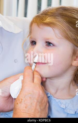 3 Jahre altes Kind, mit ihrer Mama/Mutter, erhält Dosis der Fluenz Grippeimpfstoff Nasenspray Immunisierung von - Stockfoto