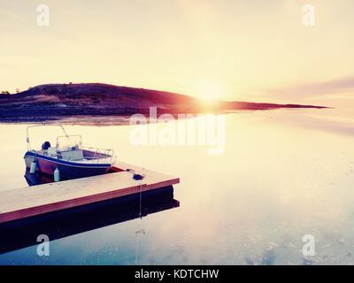 Motorboot für die Sportfischerei zu einem hölzernen Schwimmdock gebunden. Fischerboot mit Angelruten in Kleiderbügel - Stockfoto