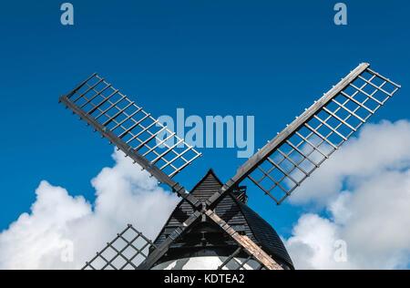Windmühle, mit schwarzen Segel, Holz- lamellendach gegen den blauen Himmel mit Fluffy Clouds - Stockfoto
