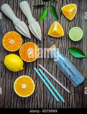 Saft mit Entsafter und Glas Flasche. frische Zitronen, Limetten und Orangen auf schäbigen Holztisch mit Flach. - Stockfoto
